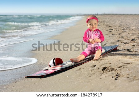 Little baby girl on the sand beach with surf board. Holiday concept - stock photo