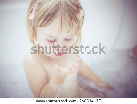 Little baby girl playing with bubbles in the batc - stock photo