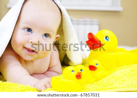 Little baby girl playing with rubber duck - stock photo