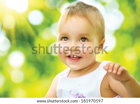 Little Baby Girl Portrait outdoor. Cute Child over nature background. Smiling adorable one year old baby. Sunny day - stock photo