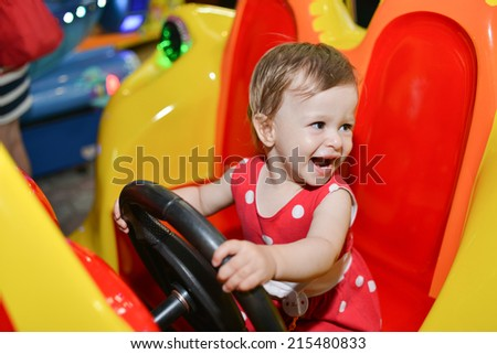 Little baby girl riding a car in amusement park  - stock photo