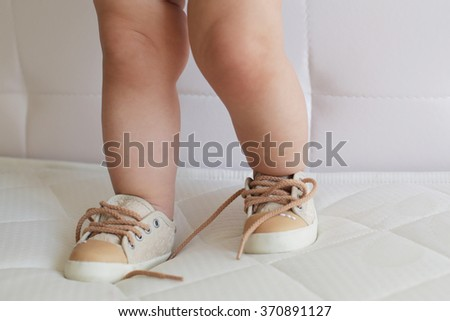 little baby girl's feet in sneakers - stock photo