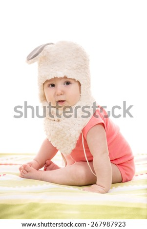 Little baby girl sitting  and wearing bunny hat isolated on white background - stock photo