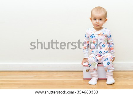 little baby girl sitting on box sleeping suit surprise   - stock photo
