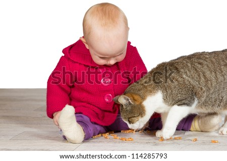 Little baby girl sitting on the floor with the family cat who is standing between her outstretched legs eating kitty treats - stock photo