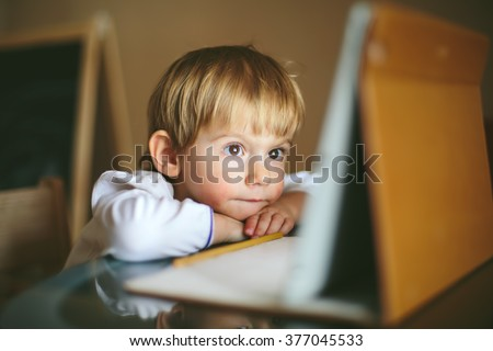 Little baby Girl sitting with tablet looking cartoons - stock photo