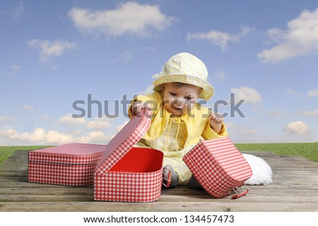little baby girl with red and white vintage suitcases, outdoors - stock photo