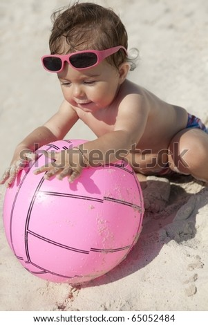 Little baby girl with thumbs-up gesture on the sand beach with pink sunglasses and ball - stock photo
