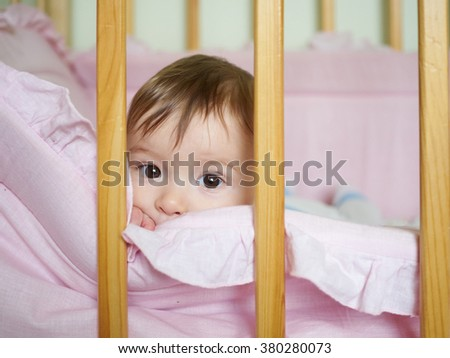 Little baby in a cot. Portrait child baby close up. - stock photo