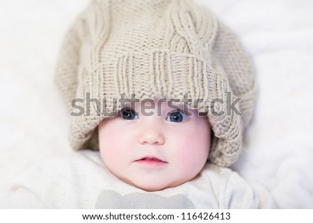 Little baby in a huge knitted hat - stock photo