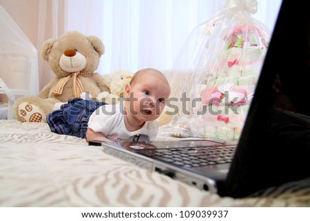 little baby in bed with laptop - stock photo