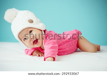 Little baby in knit winter clothing closing face with knitted beanie - stock photo