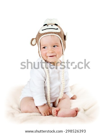 little baby in knitted monkey hat on brown blanket - stock photo