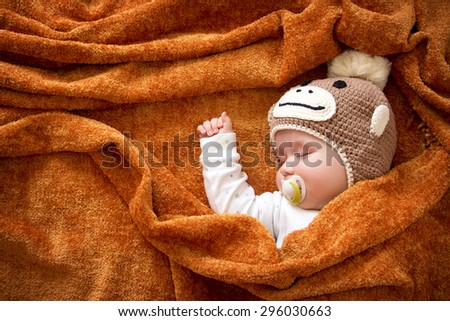 little baby in knitted montey hat on brown blanket - stock photo