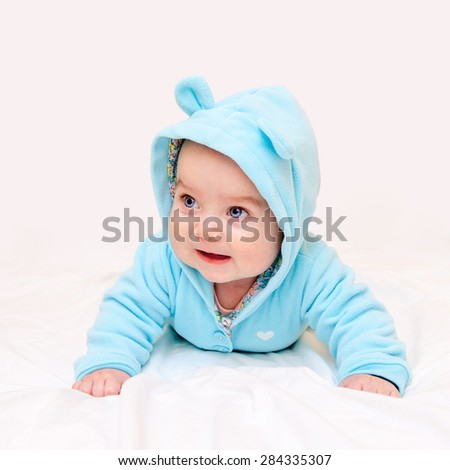 Little baby in turquoise clothes lying on his tummy with his head up on light pink sheet background. Selective focus on baby face.  - stock photo