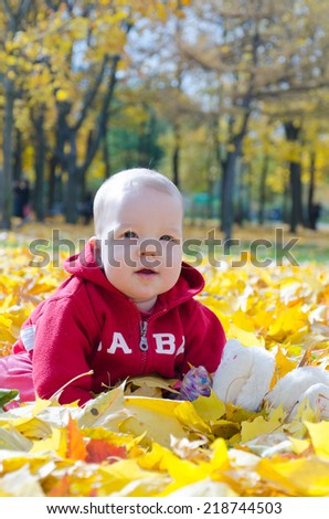 Little baby in yellow autumn leaves - stock photo