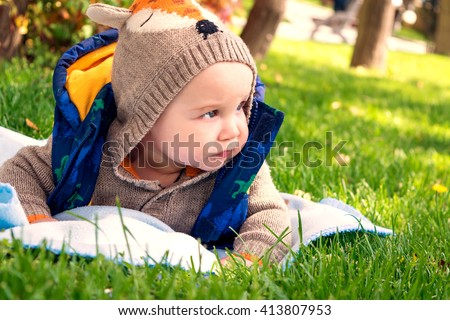 little baby is 6 months lying on the grass in the spring - stock photo