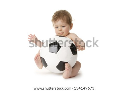 Little baby is playing with a football. - stock photo