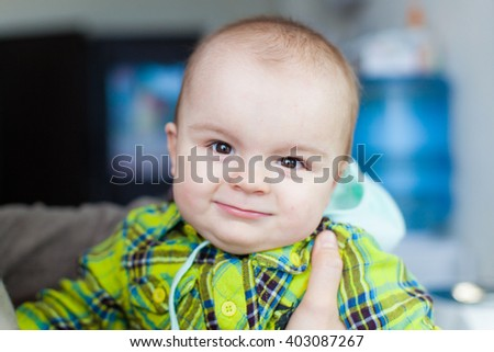 Little baby makes faces at the background of water cooler, closeup portrait, smiling, nice,  moving, heartwarming - stock photo