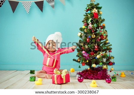 Little baby open the gift box with Decorating Christmas tree on green background - stock photo