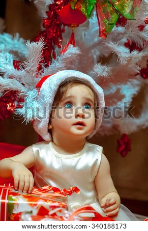 Little baby opens present under the Christmas tree. Christmas mood. New year. - stock photo