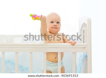 Little baby playing on bed at home with toy - stock photo