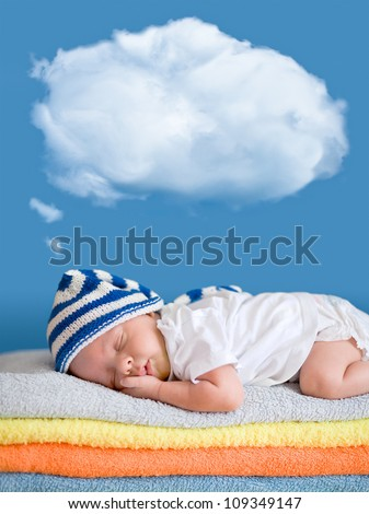 Little baby sleeping on stack of colorful towels with a dreaming balloon above - stock photo