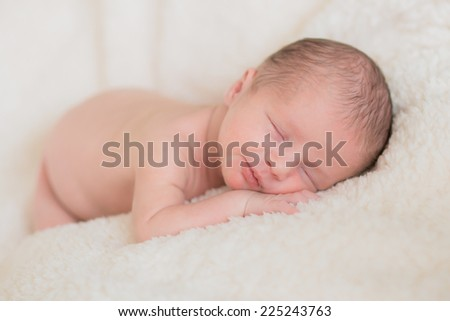 little baby sleeping peacefully on a soft bed cover - stock photo