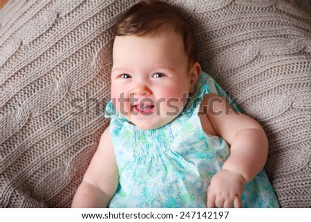 little baby smiling on a blanket  - stock photo