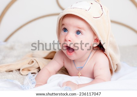 Little baby smiling under bath towel - stock photo