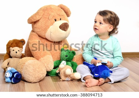 Little baby toddler playing and laughing with his teddy bears. Cute boy having fun with his big family of teddy bear toys - stock photo