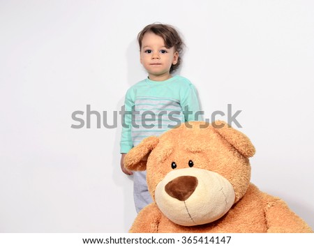 Little baby toddler playing with his big teddy bear. Cute boy standing sad waiting behind his big teddy toy. - stock photo