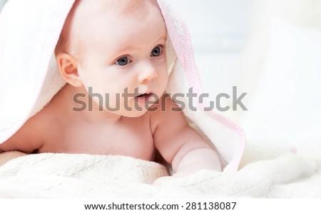 Little baby under rose towel. Studio shot - stock photo
