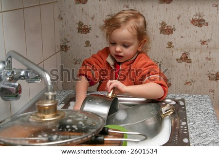 Little baby washing the dishes in the kitchen - stock photo