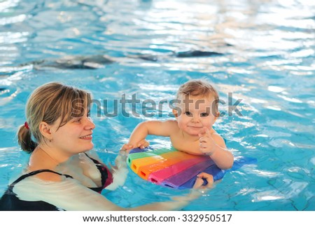 Little baby with blue eyes learning to swim with mother. Indoor swimming pool. Healthy childhood and growth of children - stock photo