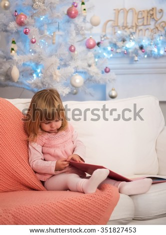 Little Baby with book near the Christmas tree - stock photo