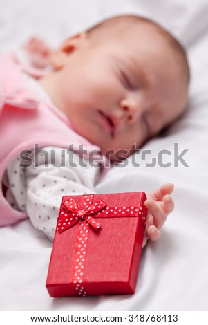 Little baby with christmas gifts around on white background - stock photo