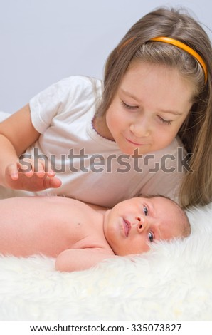 Little baby with her sister - stock photo