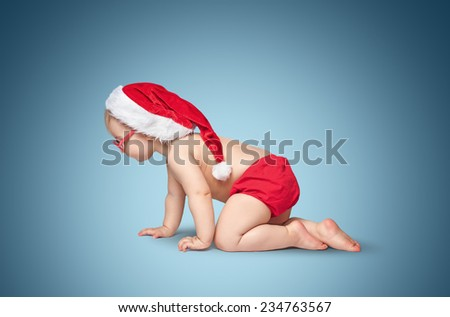 little baby with Santa hat and glasses crawling on blue background. - stock photo