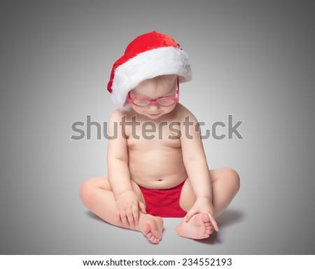 little baby with Santa hat and glasses sit on color background - stock photo
