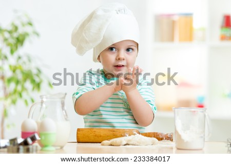 little baker child girl in chef hat at kitchen - stock photo
