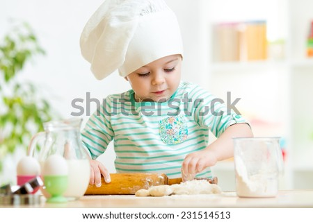 little baker kid girl in chef hat at kitchen - stock photo