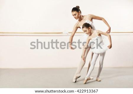 Little ballerina dancing with ballet teacher in dance studio - stock photo