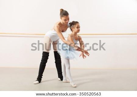 Little ballerina dancing with personal ballet teacher in dance studio. Teacher helping little ballerina to make a right elegant move - stock photo