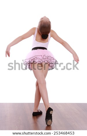 little ballerina in a pink tutu standing back to camera  - stock photo