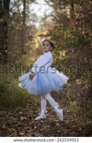 Little ballerina in autumn park - stock photo
