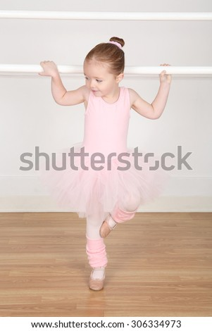 Little ballerina wearing a tutu dancing at the barre - stock photo