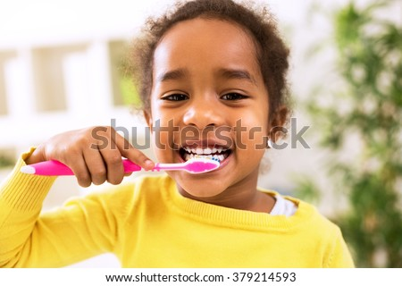 Little beautiful african girl brushing teeth, healthy concept - stock photo