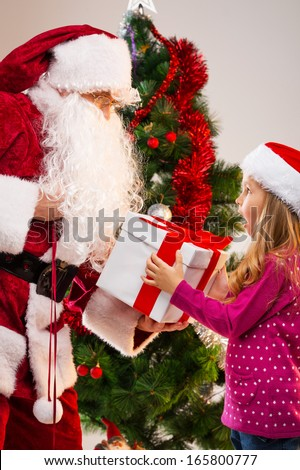 Little beautiful blond girl getting present from Santa Claus. Looking happy and surprise with Christmas tree on background  - stock photo