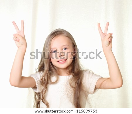 Little beautiful blond girl shows sign victory on both hands and smile - stock photo